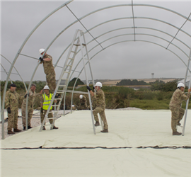 Personnel from 14 Squadron, Royal Logistic Corps (RLC) construct accommodation